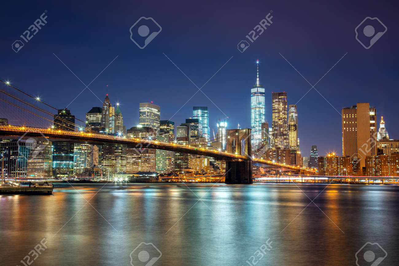 New York - view of Manhattan Skyline with skyscrapers and famous Brooklin Bridge by night and city illumination, USA - 58149535