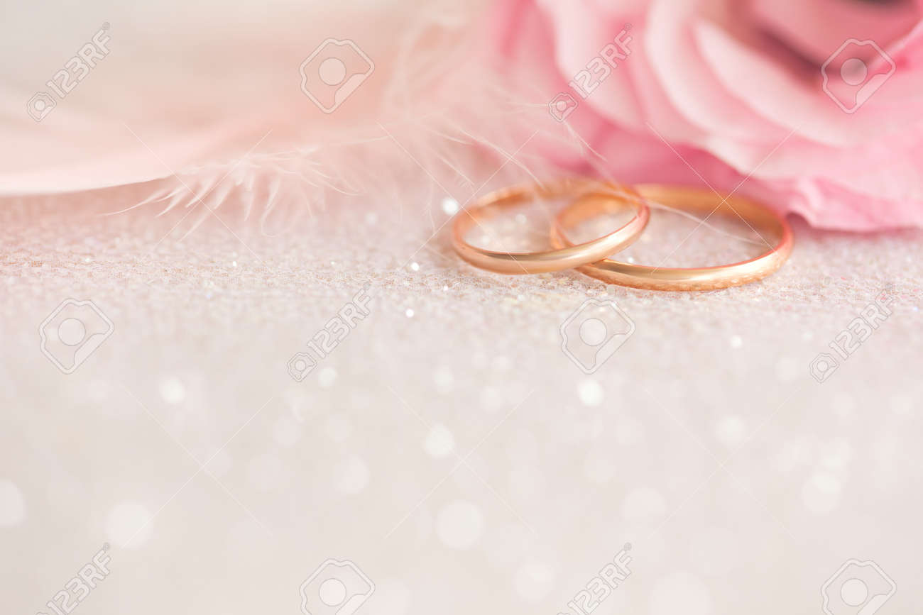 Gentle Wedding Background With Gold Rings Pink Flower And Light