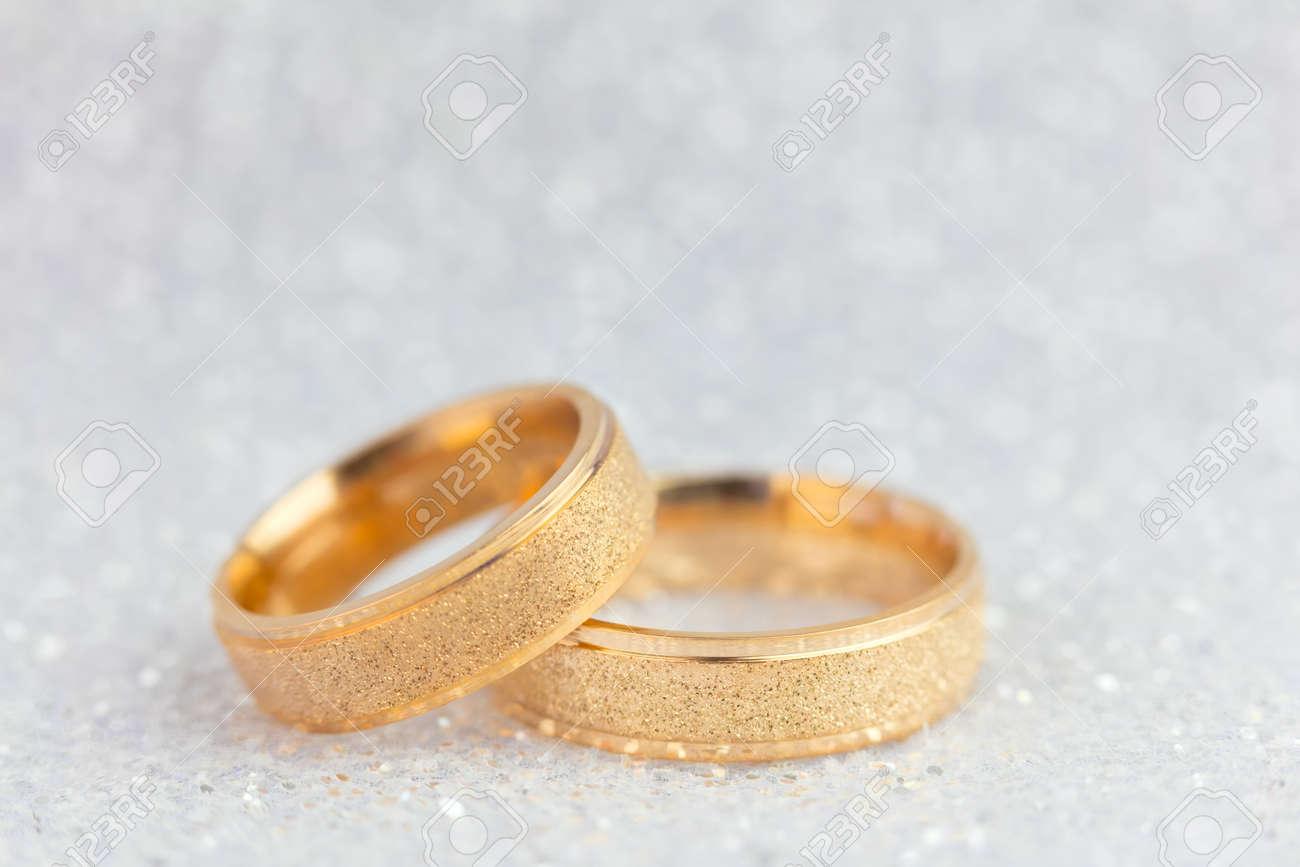 Sparkling Wedding Background - Two Golden Wedding Rings on gentle light glitter background - 73764068