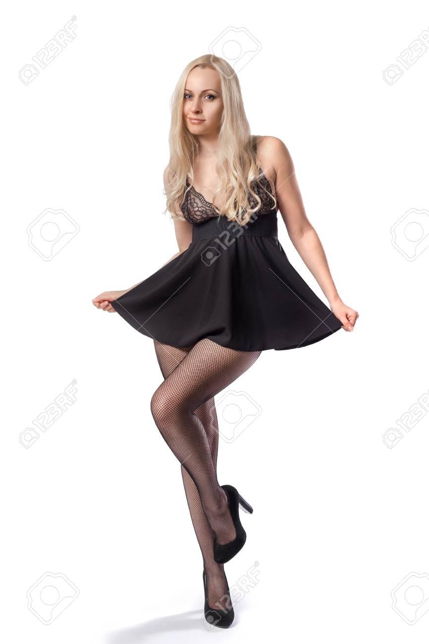 d539afb59a6 Banque d images - Modèle blonde en robe noire sexy courte et collants -  isolé sur blanc et avec une ombre sur le sol