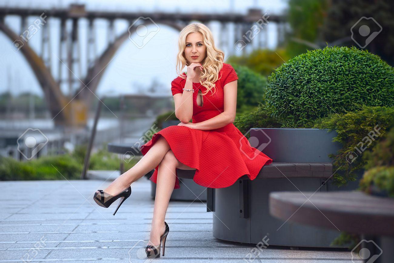 c46fd4d72f2d Archivio Fotografico - Bella donna bionda in abito rosso e tacchi alti è  seduto all aperto sulla panchina alla sera.