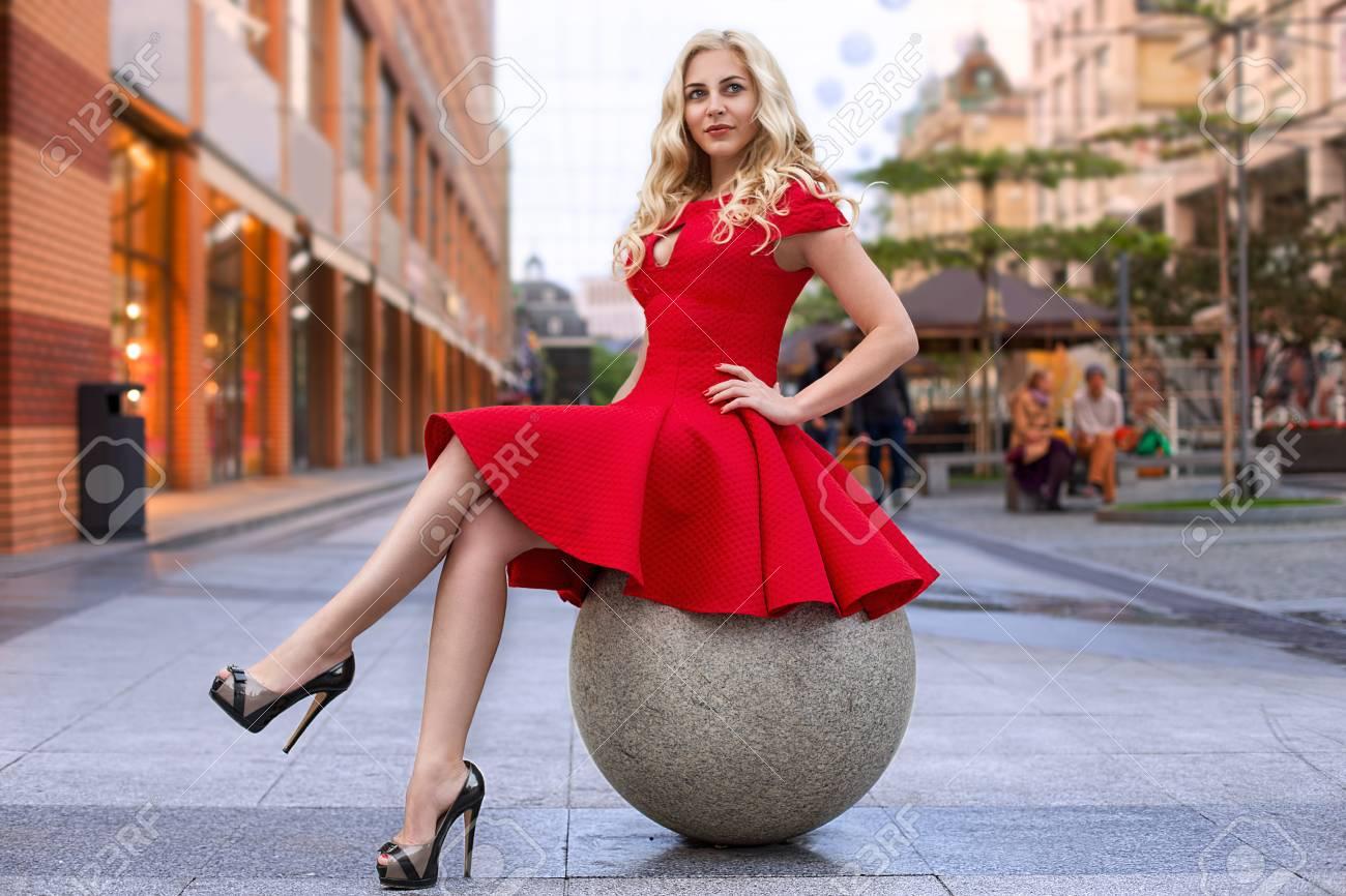 new product 65cb3 f7f66 Bella donna bionda in abito rosso e tacchi alti è seduto all'aperto sulla  sfera di pietra alla sera.