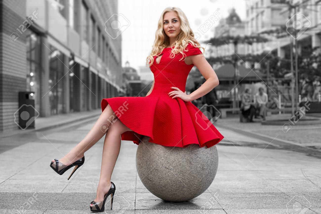 Mujer Rubia Hermosa En Vestido Rojo Y Zapatos De Tacón Alto Está Sentado Al Aire Libre En La Esfera De Piedra Al Aire Libre En Blanco Y Negro