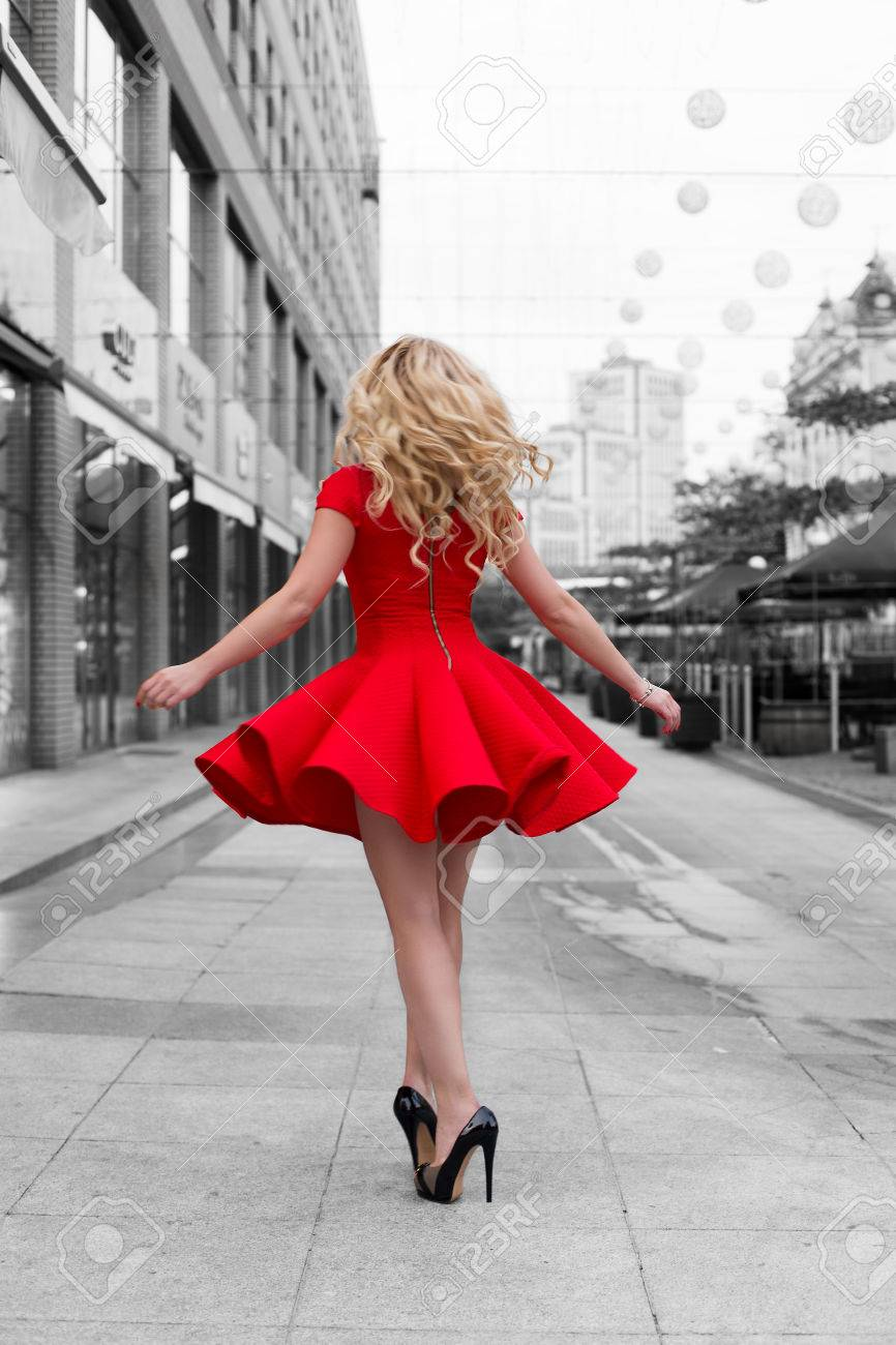 36f6dfa3987 Beautiful blonde woman in the red dress and high heels walking..