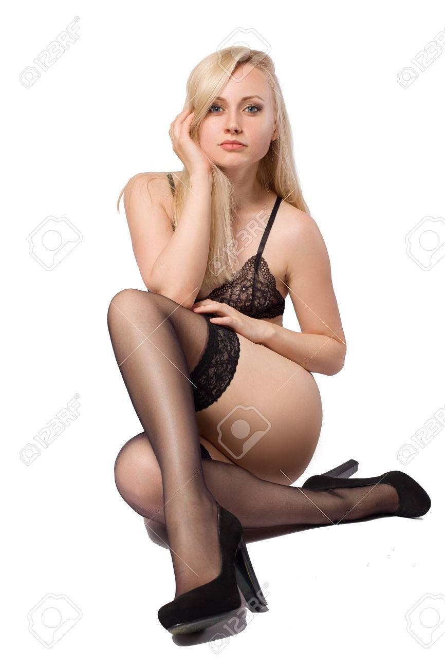 a5b9c130d Hermosa mujer rubia posando en medias negras y lencería y tacones aislados  sobre el fondo blanco con las sombras en el suelo