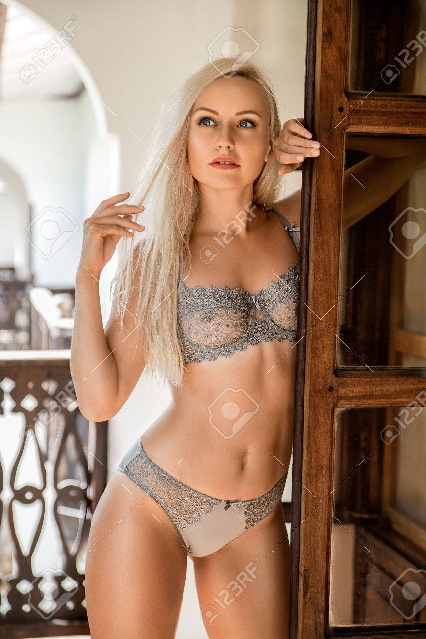 beautiful blonde woman in lingerie posing on the old african.. stock