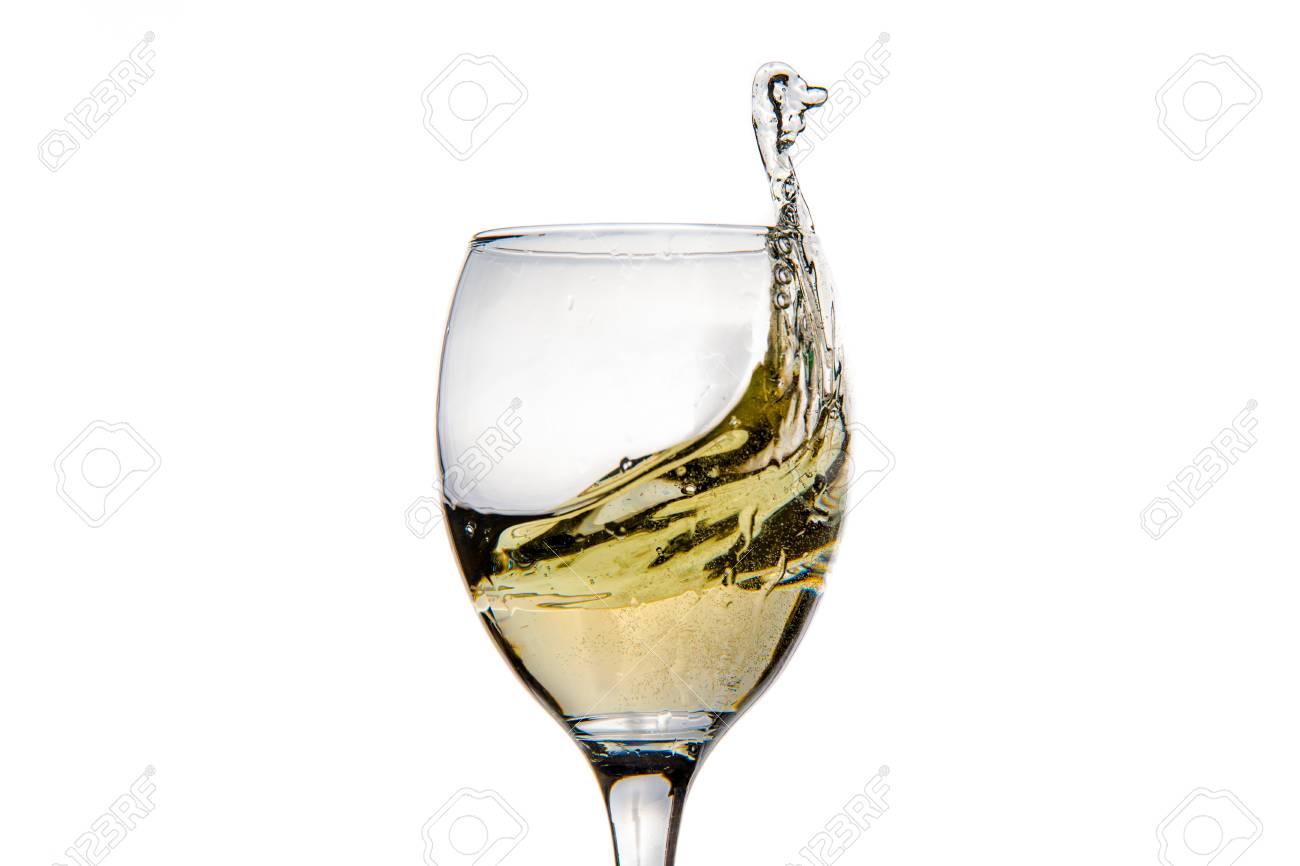 Verre à vin avec éclaboussures de gouttes de champagne image de gros plan de mouvement gel isolé sur le fond blanc.