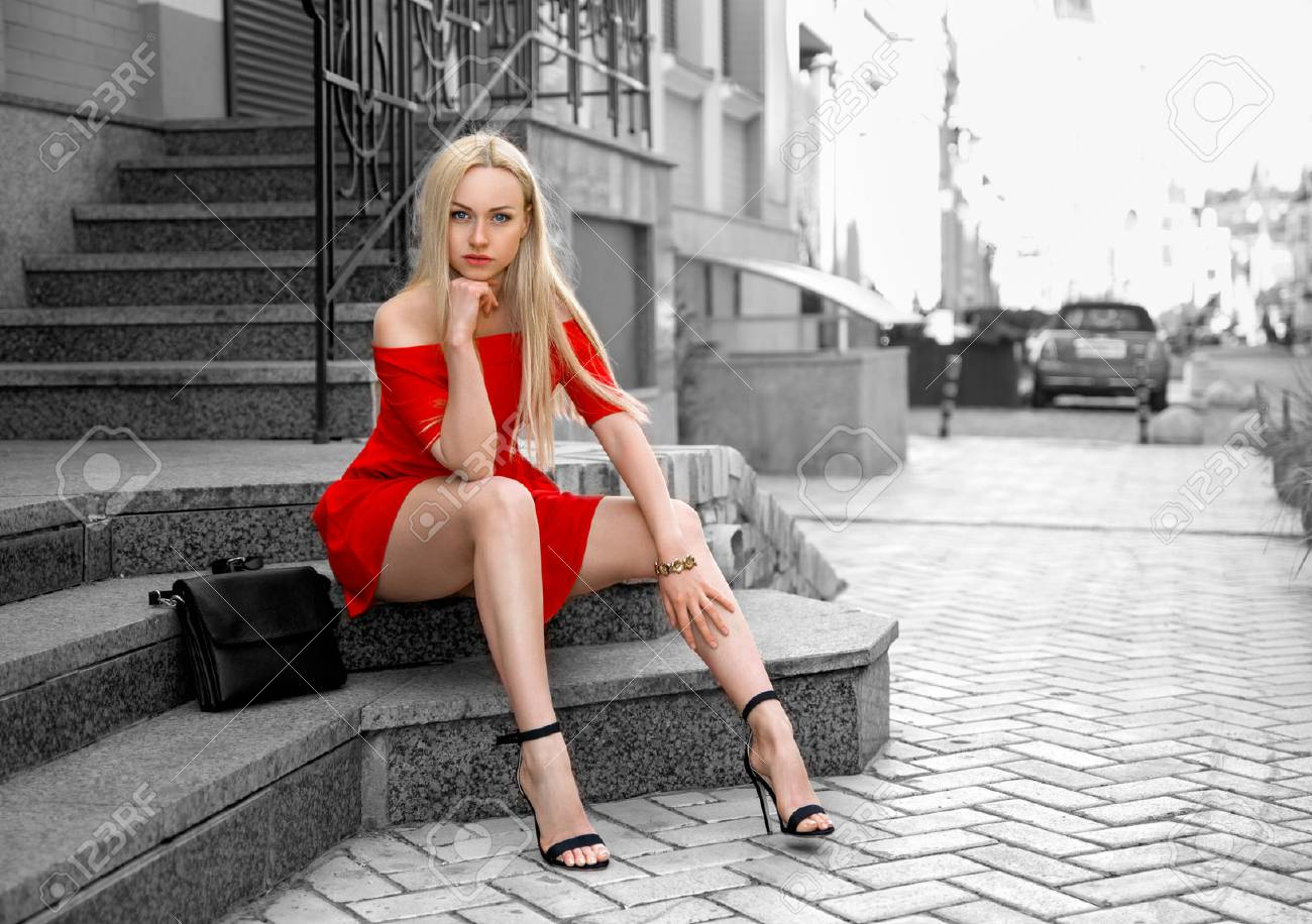 6561c41e283 Beautiful blonde woman in red dress and high heels sitting outdoor..