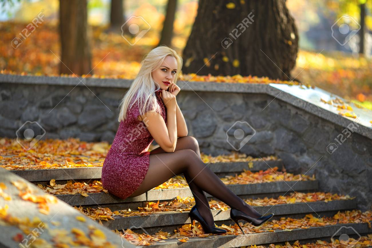 Beautiful blonde girl with perfect legs posing outdoor on the street of autumn park in the lights of setting sun. - 110350442