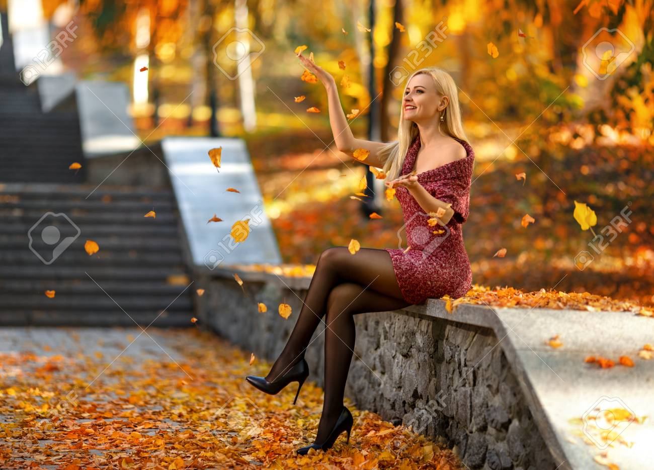 Beautiful blonde girl with perfect legs playing with fallen leaves on the street of autumn park in the lights of setting sun. - 110521811