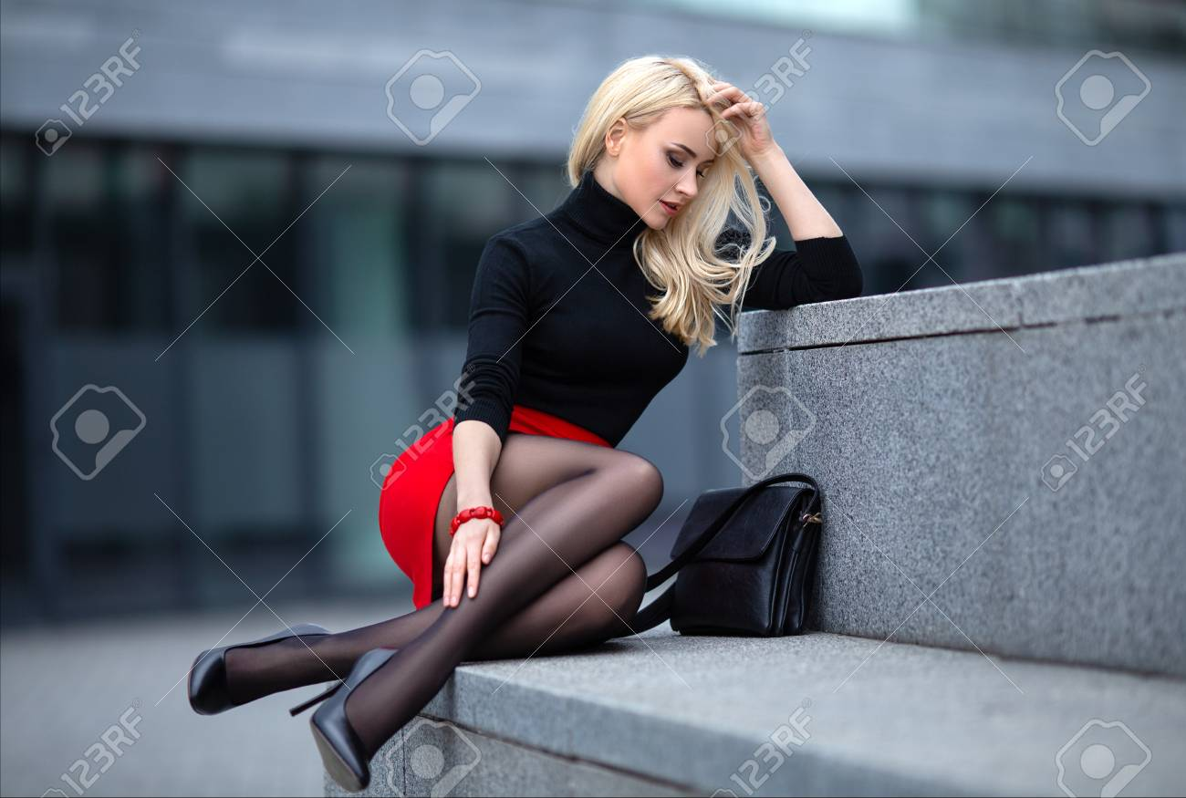 Beautiful blonde girl in red skirt with perfect legs in pantyhose and shoes with high heels posing outdoor on the city square. - 120644863