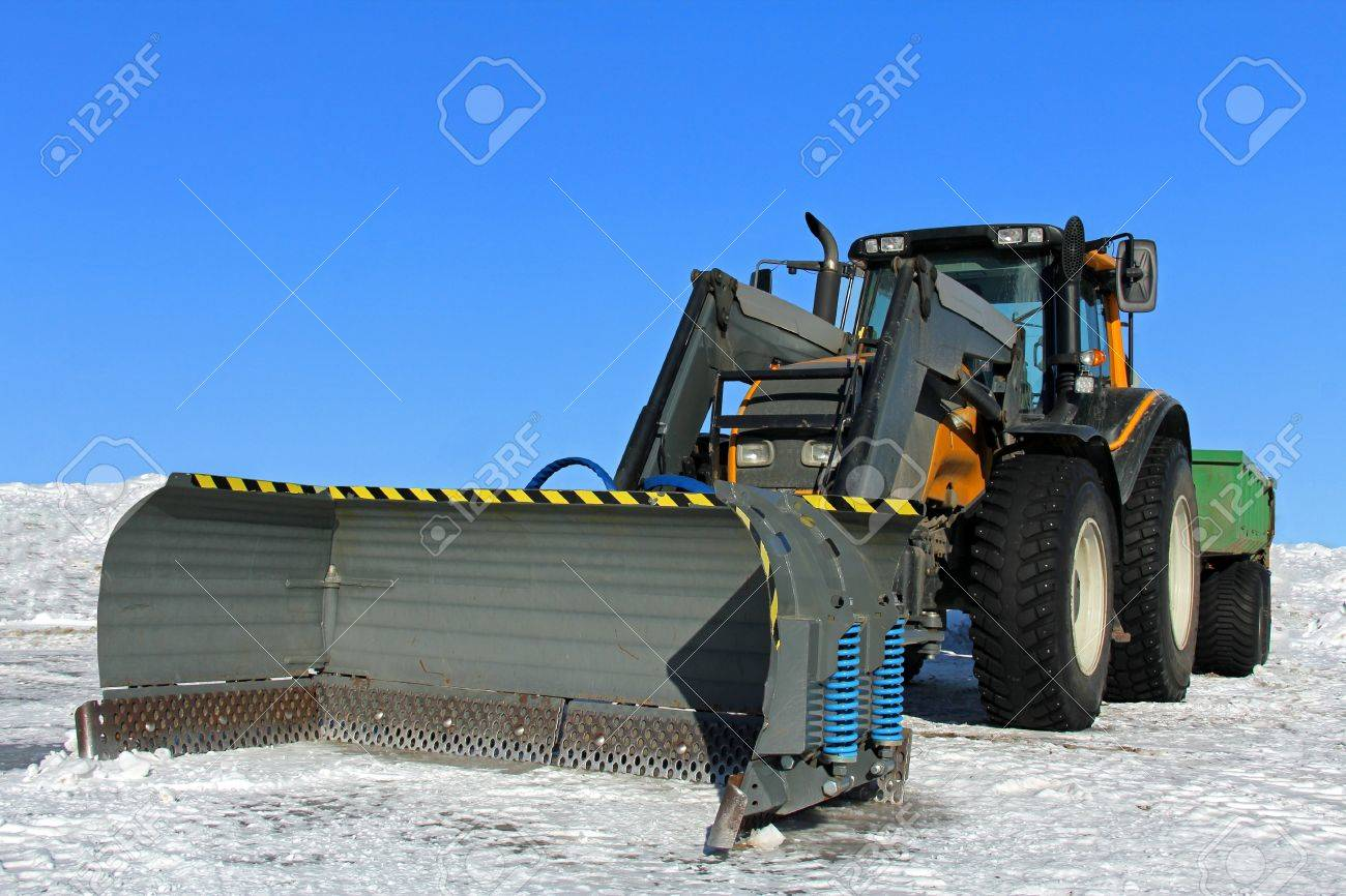Snow plow mounted on a yellow tractor with snow and blue sky
