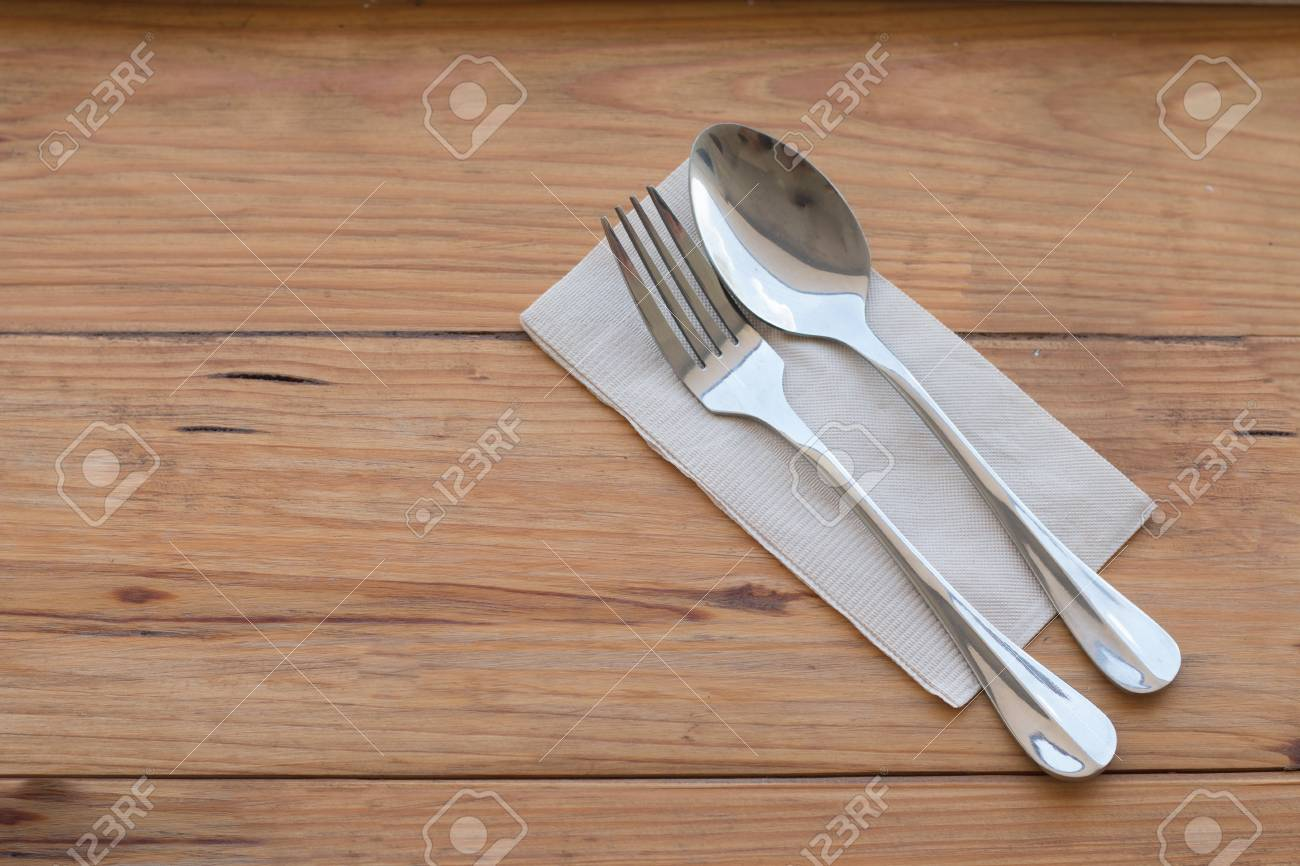 Silverware, fork spoon and paper put on wooden dining table