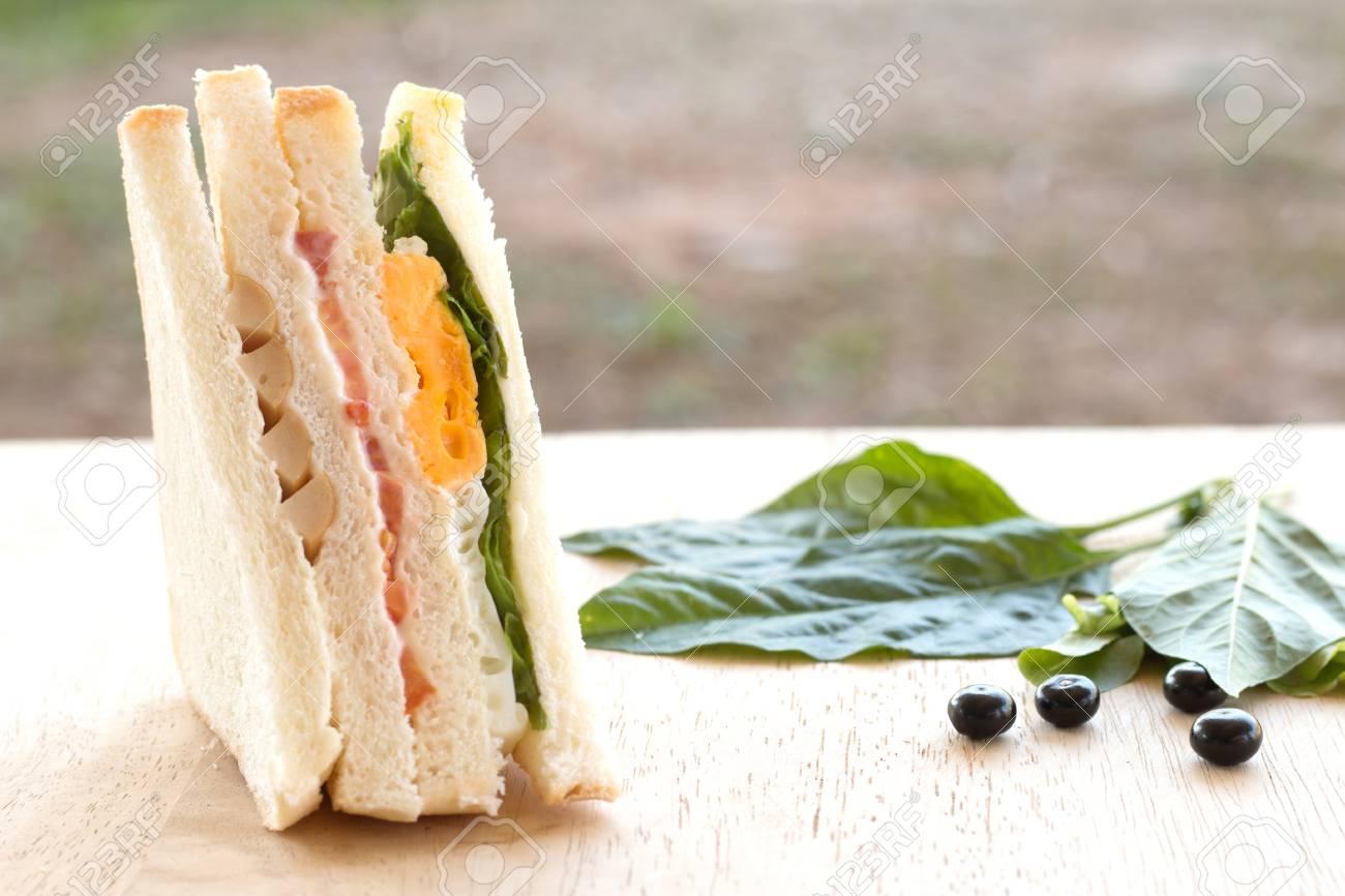 Sandwich fait maison avec des baies sur un bureau en bois banque
