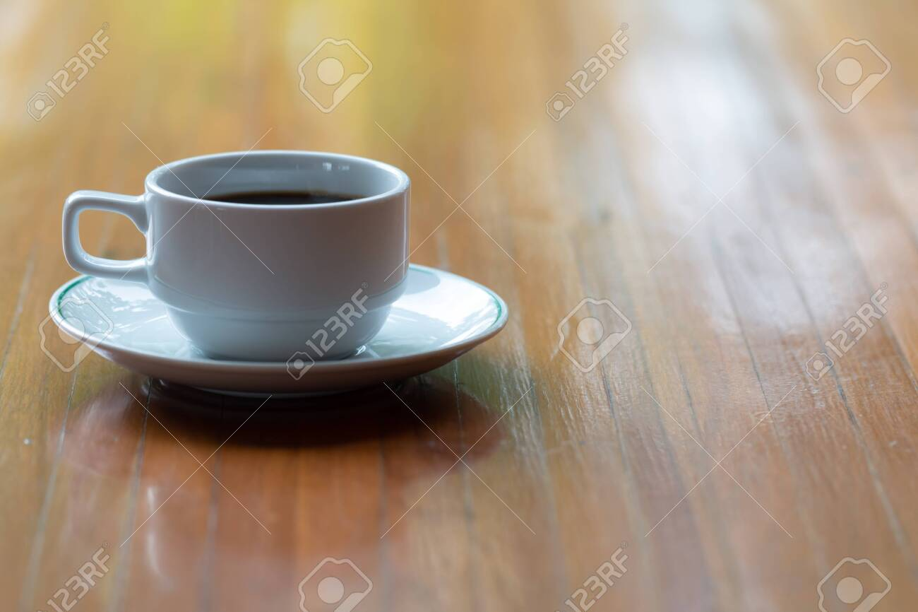 Close up a cup of hot coffee on wooden table. - 126964144