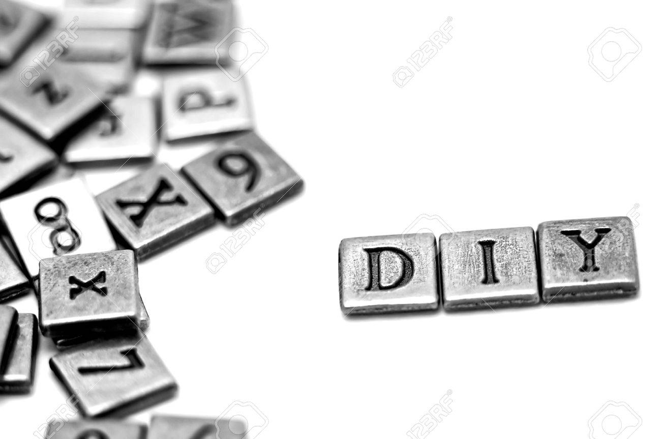 Metal scrapbooking letters spelling DIY: Do It Yourself. They lay on a white background and there is a bunch of other letters laying by. Stock Photo - 18483109