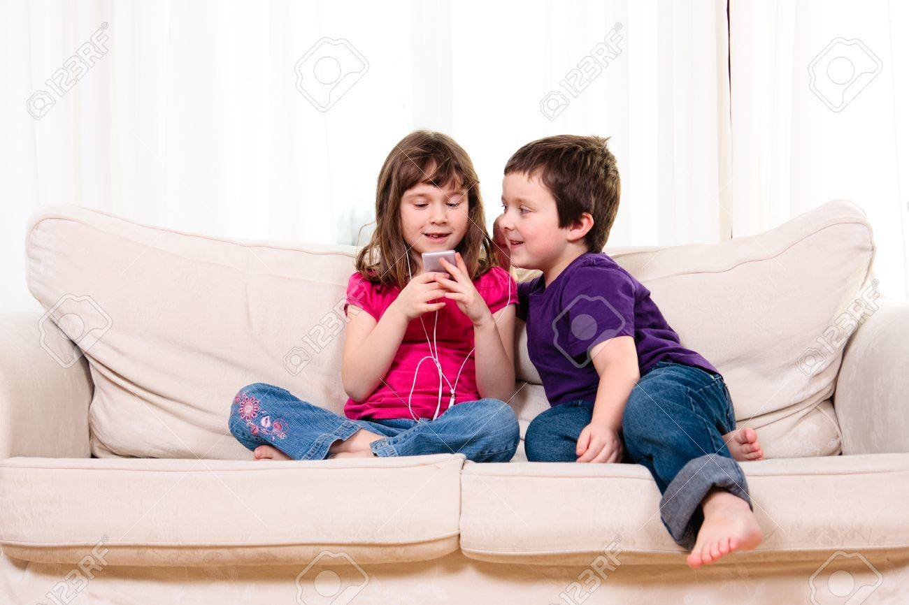 Children listening to music while sitting on a couch Stock Photo - 18576884