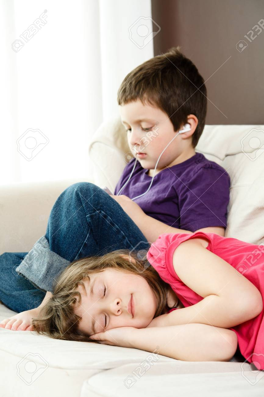 Girl taking a nap while her brother listen to music Stock Photo - 18577739