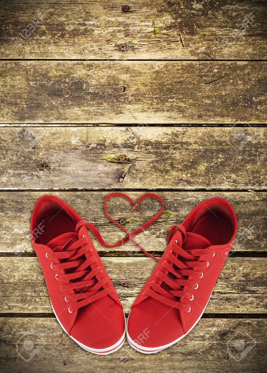 Heart Shaped Red Shoelaces Of Sneakers On Wooden Deck Stock Photo
