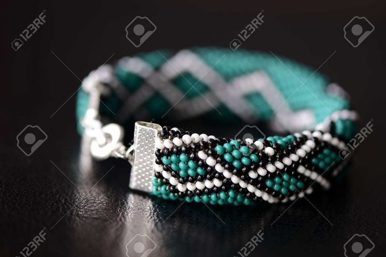Green Bead Crochet Bracelet With Celtic Print On A Dark Background