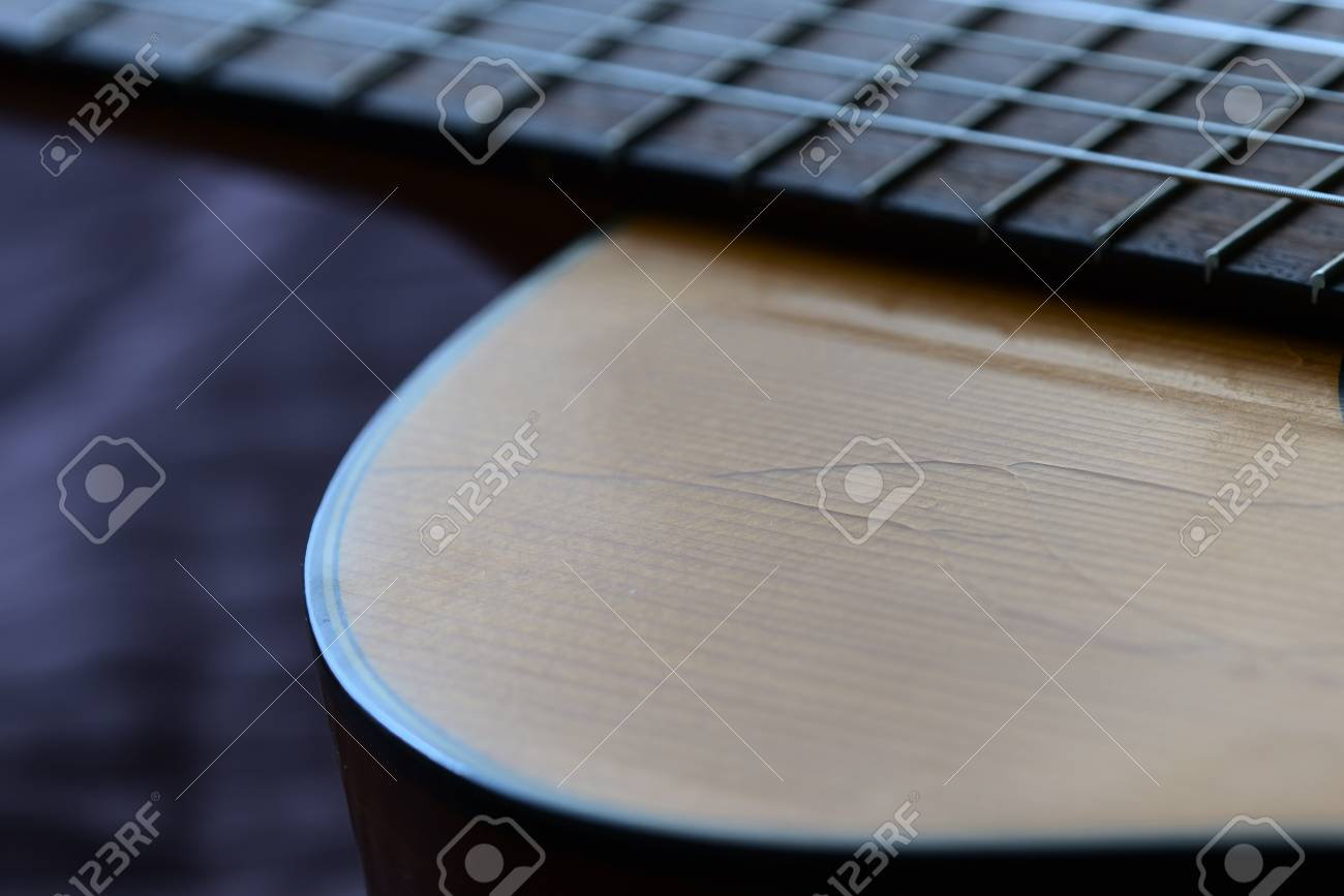 Old acoustic guitar with cracks on the soundboard close up