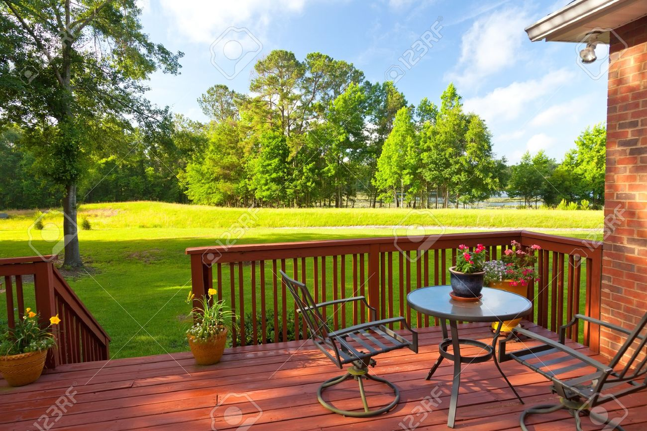 Residential backyard deck overlooking lawn and lake - 20864956