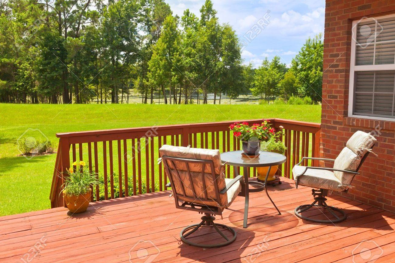 Residential backyard deck overlooking lawn and lake - 20933355