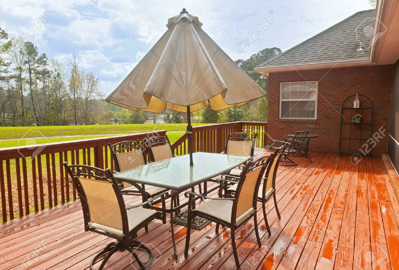 Large wooden backyard deck with patio furniture and a view of lake - 22283818