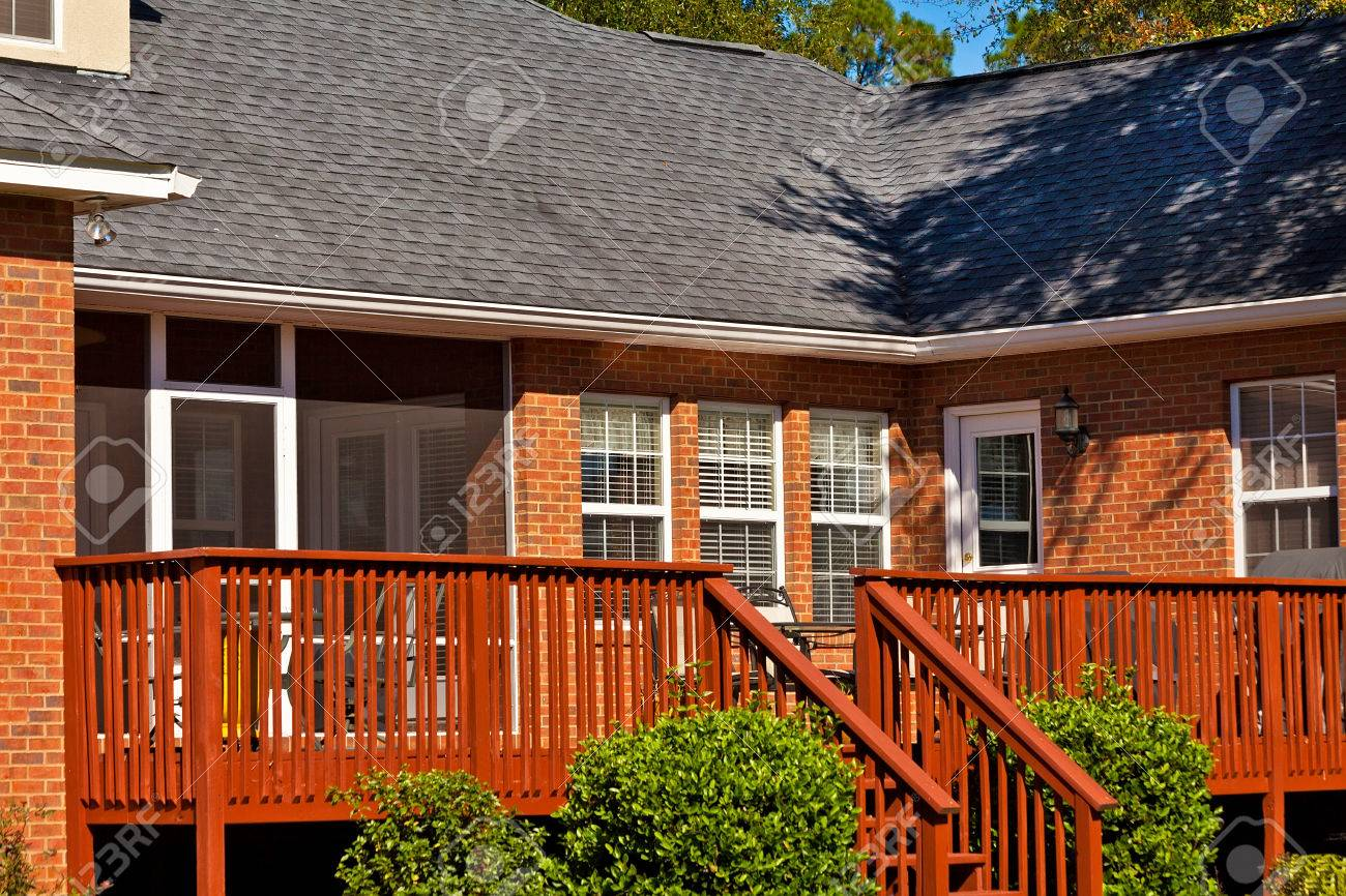 Attaching deck to house with siding - Stock Photo Wooden Backyard Deck Attached To Residential House