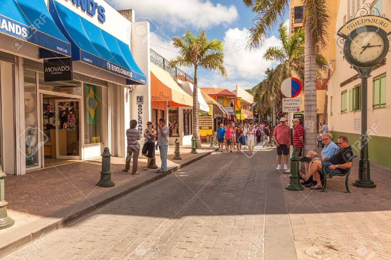 Philipsburg, St. Maarten - Jan. 19, 2011: Tourists shop along the busiest street in Philispburg, Front Street, for local souveniers and bargains. Most visitors are cruise passengers and only in port for the day. - 25220972