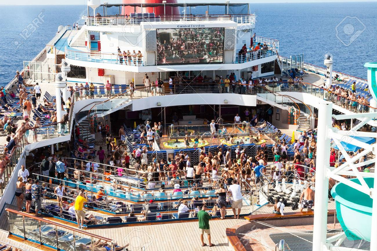 Caribbean Sea, July 10, 2011: Passengers aboard the Carnival Freedom gather on the Lido Deck at the start of a Caribbean cruise. The Freedom is the fifth 110,000-ton vessel, owned by Carnival. - 25220976