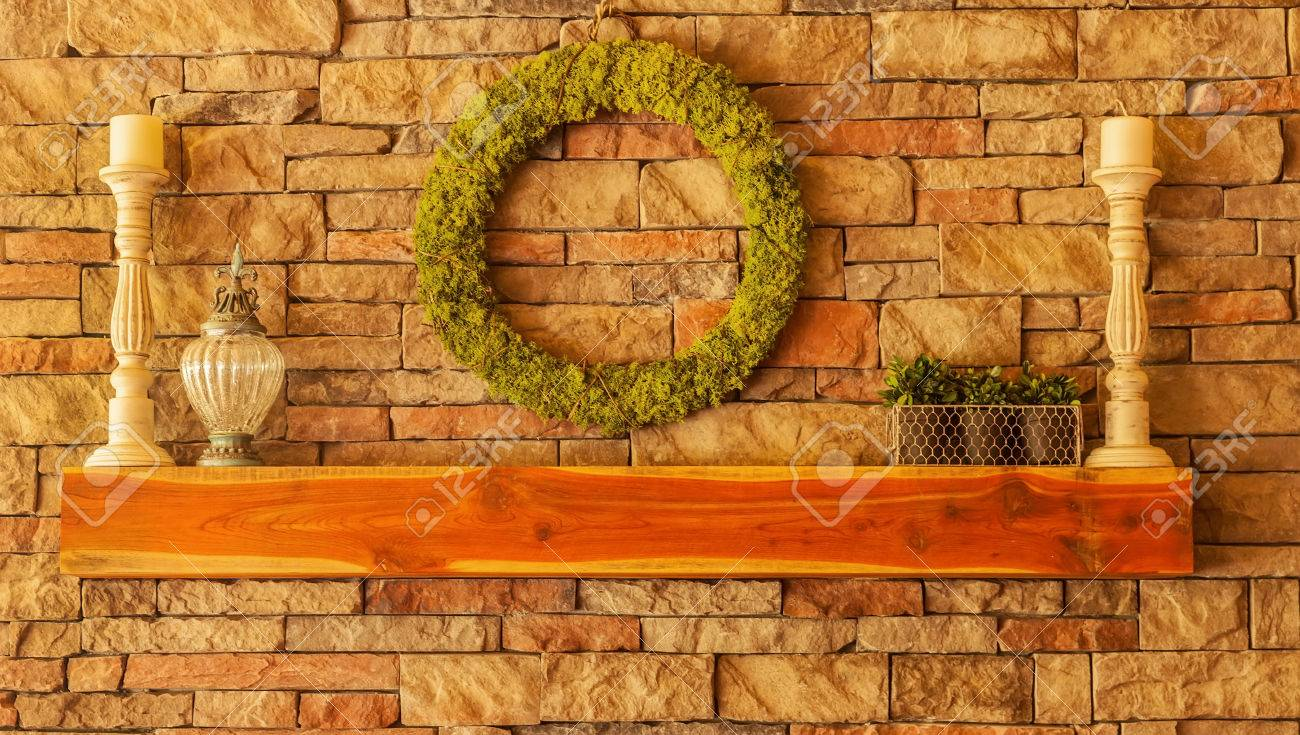 cedar wood mantel on a stone fireplace with decorations stock