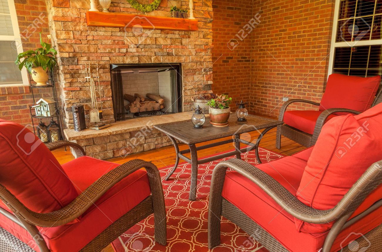 Seating area around gas stone fireplace on a covered backyard deck - 35297799