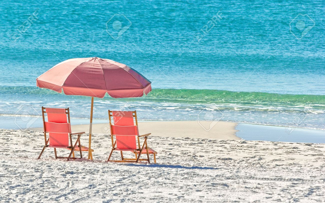 Pink Umbrella And Lounge Chairs On The Miramar Beach In Destin, Florida  Stock Photo