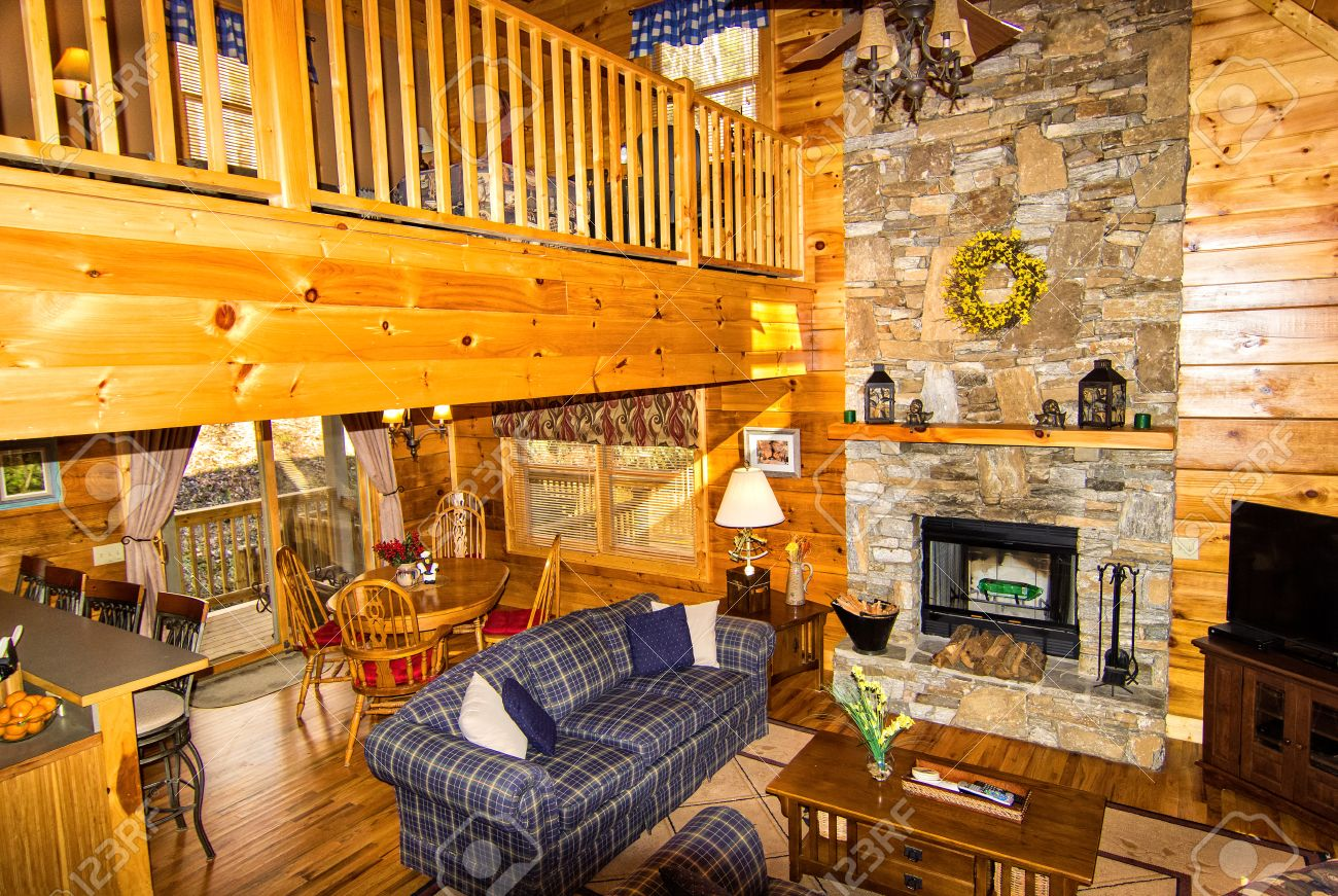 Cabin interior fireplace - Interior Of Log Cabin With Stone Fireplace Seating Area And Loft Stock Photo