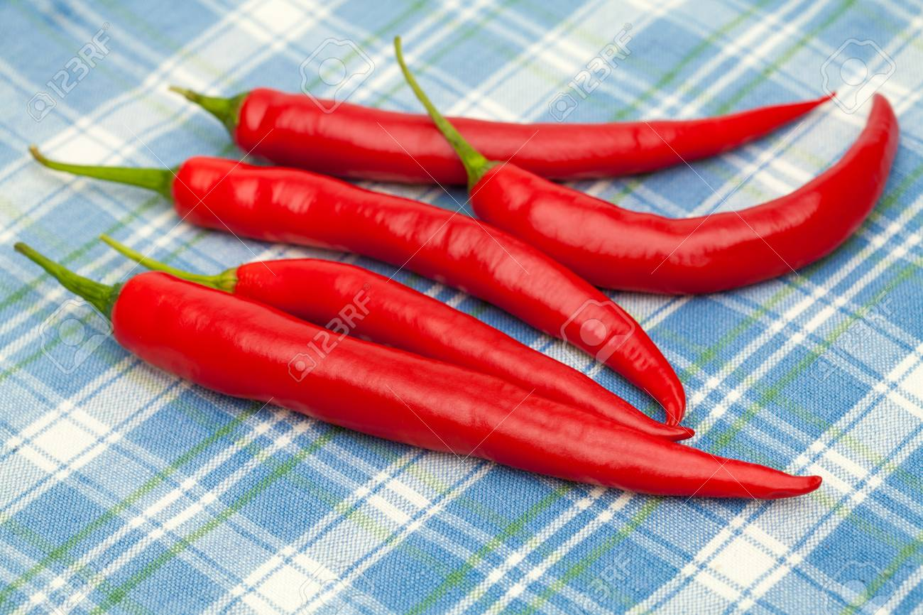 Red Chili Pepperon Blue Tablecloth Stock Photo   23438979