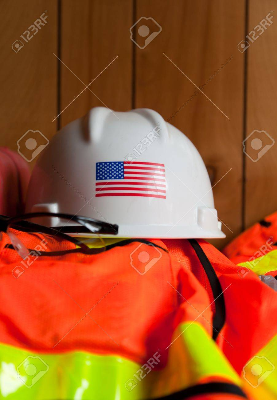 A white hard hat with the American Flag is setting on top of a orange and reflective yellow safety vest and glasses in a construction trailer. Stock Photo - 12903646