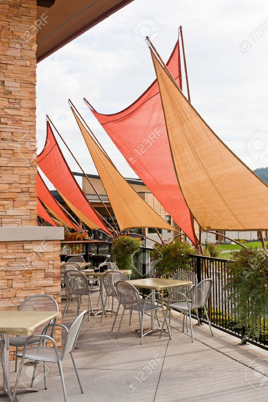 Gold And Orange Triangle Awnings Create A Shaded Area For Diners At Outdoor  Patio Chairs And