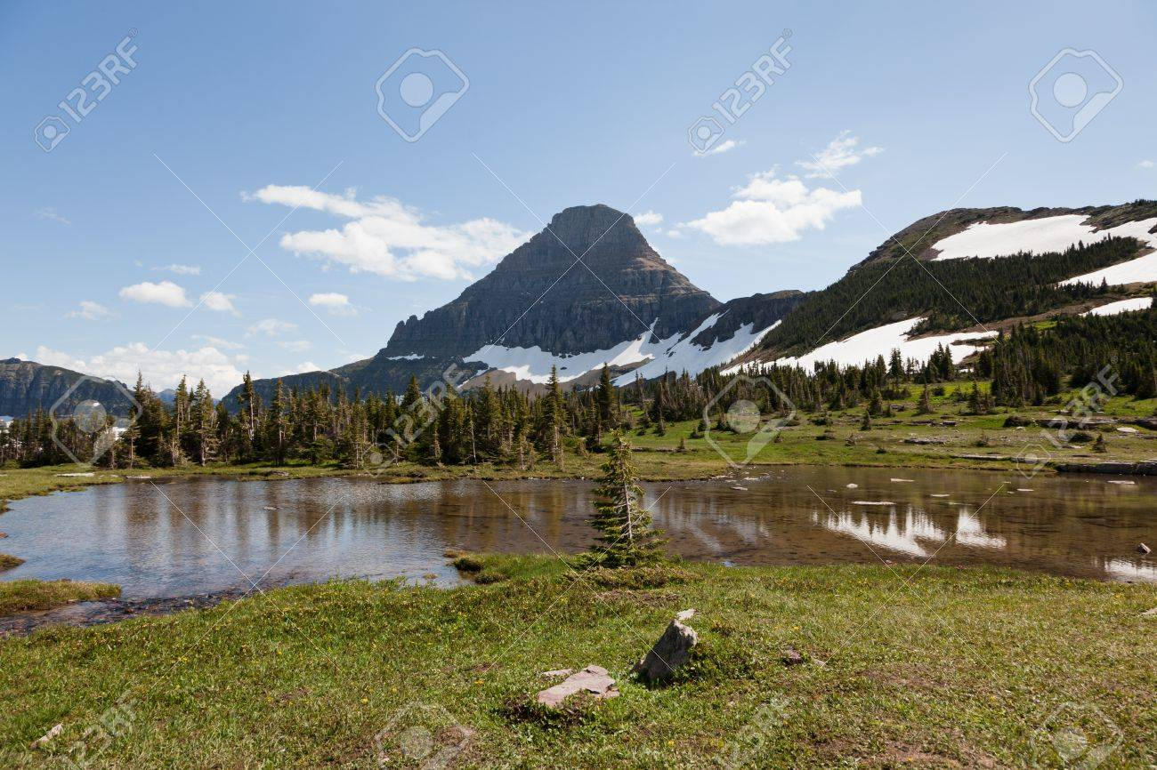 A small pond of clear water from melting snow in a meadow with large rock mountains in the distance in Glacier National Park, Montana. Stock Photo - 18334212