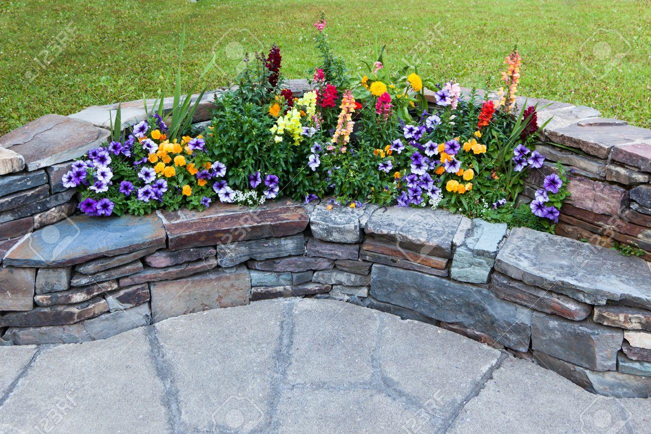 un banco de piedra curvada como decoracin de jardines con flores de verano que crece la