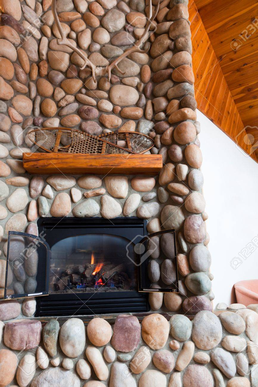 a gas fireplace set in colorful river rocks with a wooden mantle