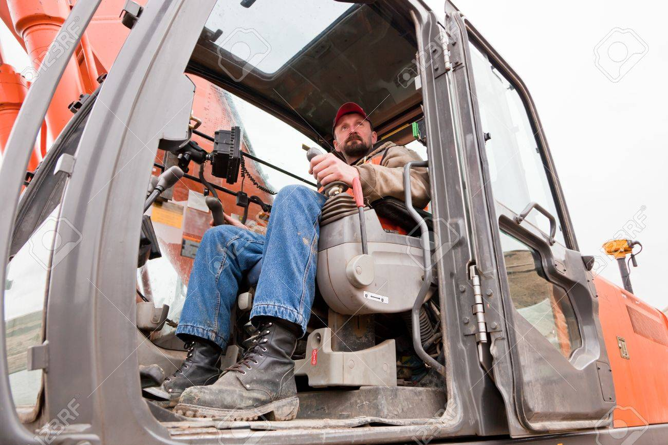 A Male Heavy Equipment Operator Sitting In The Cab Of A Track-hoe ...
