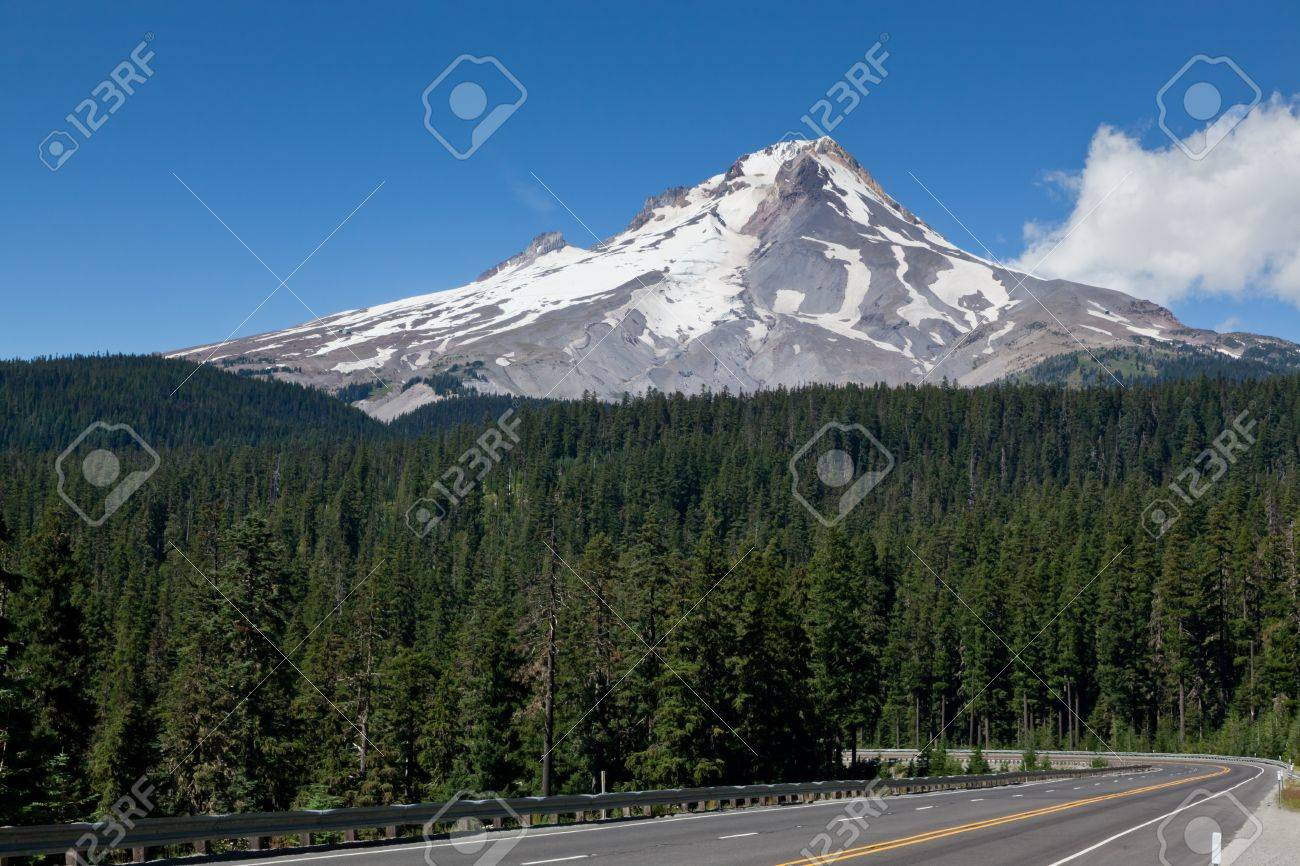 The high snowy peak of Mount Hood in Oregon towering above a lush green forest with a empty road leading into the trees. Stock Photo - 19243190