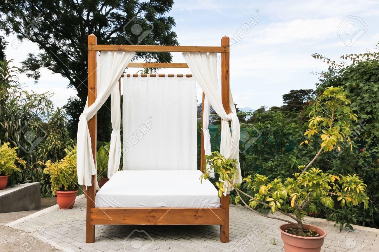 eine hölzerne outdoor bett mit weißer bettwäsche und vorhängen auf