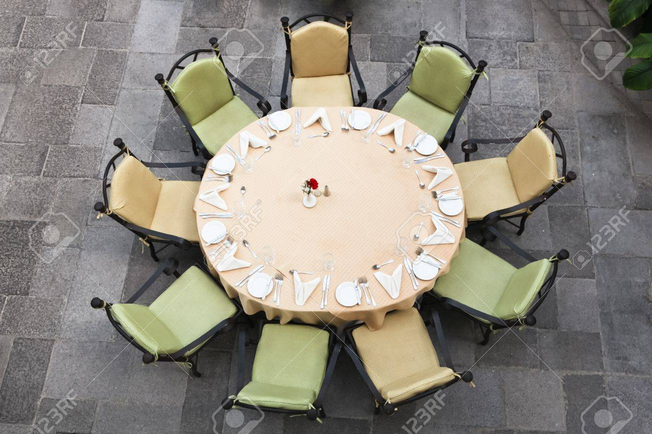 Looking down at a large round table set for nine people on a brick patio. Stock Photo - 20306543