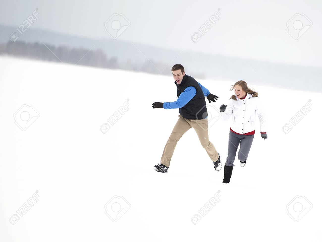 Young happy couple running through a snowy field Stock Photo - 17890315
