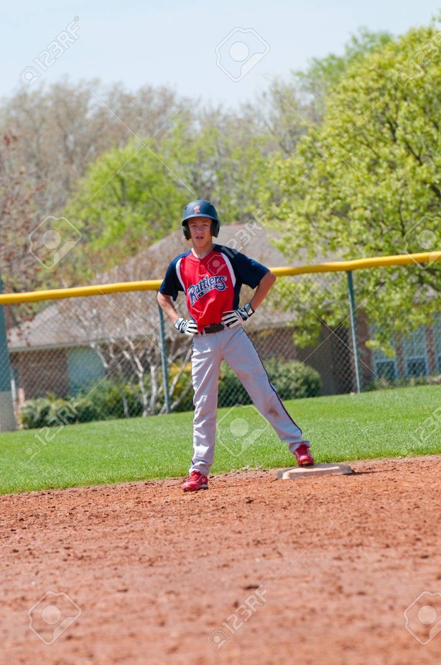 Teen baseball boy standing on second base. Stock Photo - 18971376