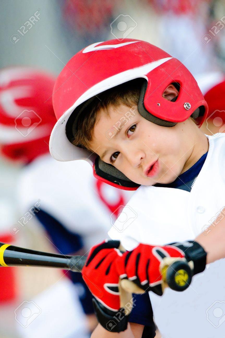 little league baseball player swinging the bat up close stock
