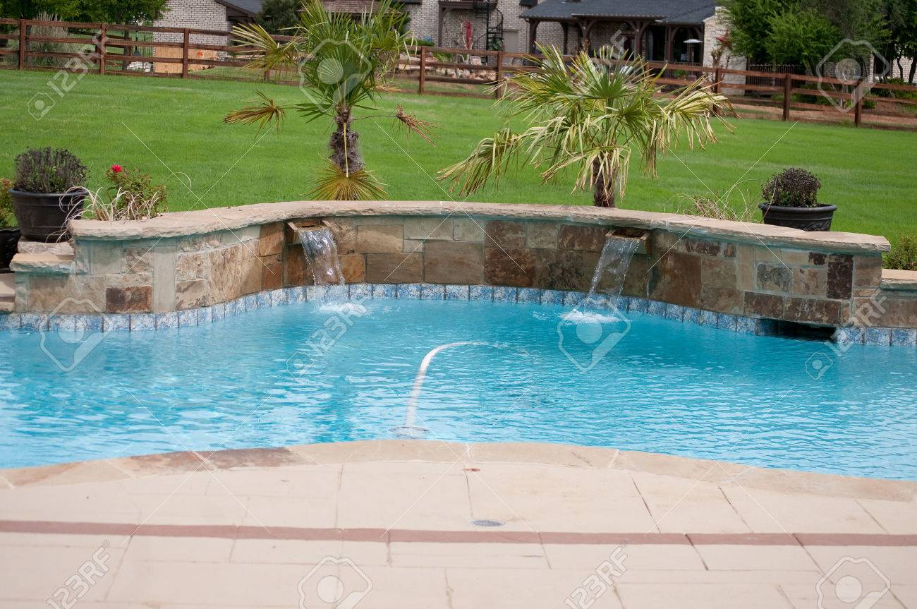 Landscaped swimming pool in residential area with waterfall.