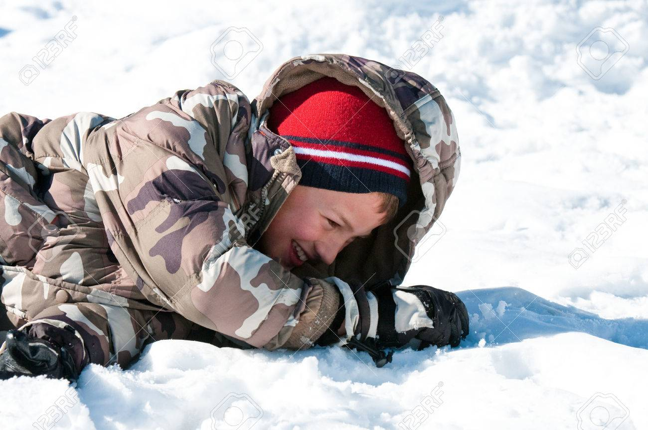 0458af822 Cute Handsome Boy Falling On The Snow In Camo Jacket Smiling.. Stock ...